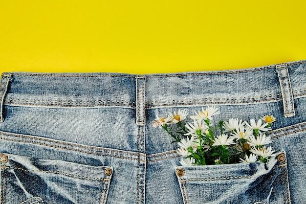 Bouquet di fiori bianchi nella tasca dei jeans
