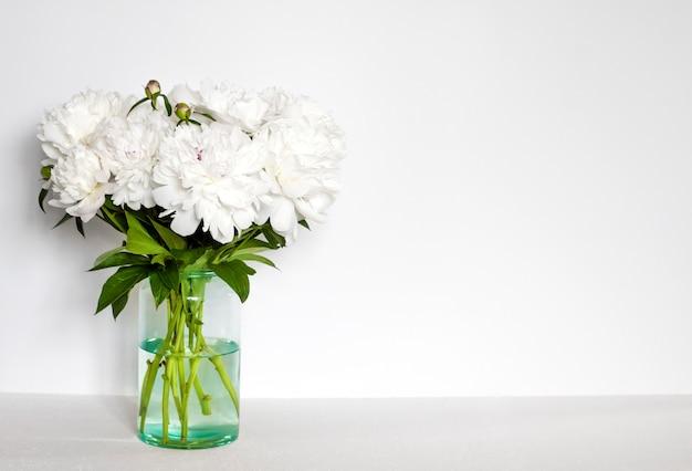 Bouquet di peonie bianche in un vaso di vetro