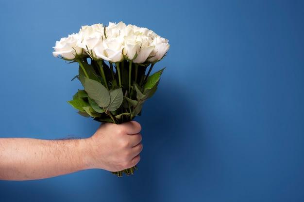 Bouquet di rose bianche in mano di un uomo su sfondo blu