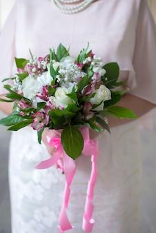 Un mazzo di rose bianche nelle mani delle donne si chiude su