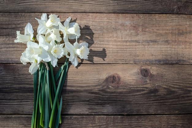Un bouquet di narcisi bianchi primaverili su un fondo di legno rustico alla luce del sole