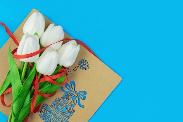 Bouquet di tulipani bianchi su sfondo blu, regalo per donna, concetto di vacanza femminile, luogo per copia spazio, vista dall'alto