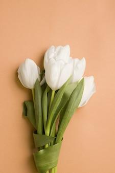 Bouquet di tulipani bianchi su sfondo marrone. vista dall'alto