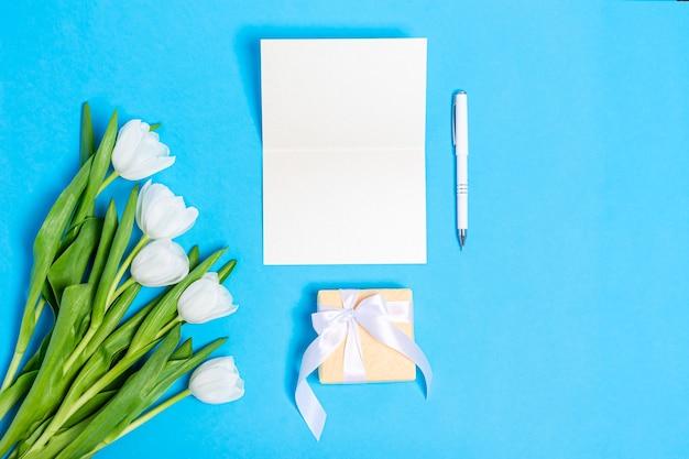 Bouquet di tulipani bianchi con scatole regalo e carta bianca su una superficie blu
