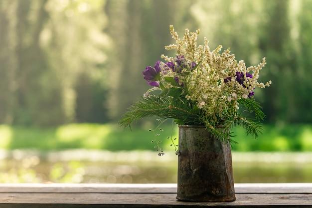 Mazzo di piante selvatiche in un barattolo di latta arrugginito su uno sfondo naturale sfocato