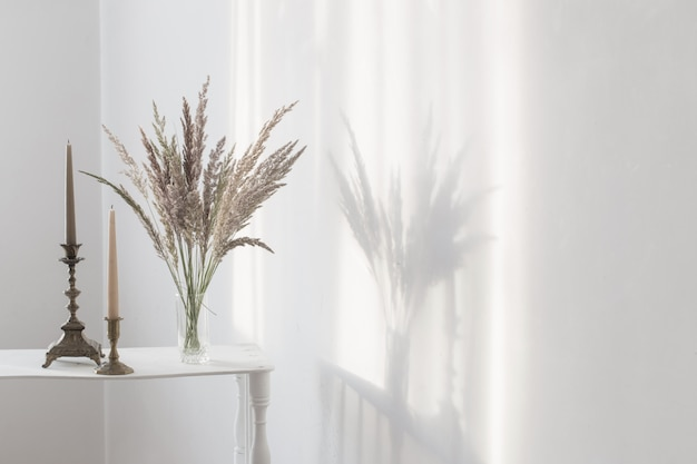 Fiori selvaggi e candele del mazzo al sole nell'interno bianco