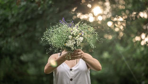 Un mazzo di fiori selvatici nelle mani di una ragazza su uno sfondo sfocato nella foresta. Foto Premium