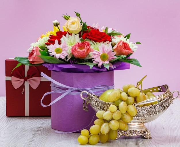 Bouquet di fiori di campo, confezione regalo e uva in un vaso di metallo su assi di legno.