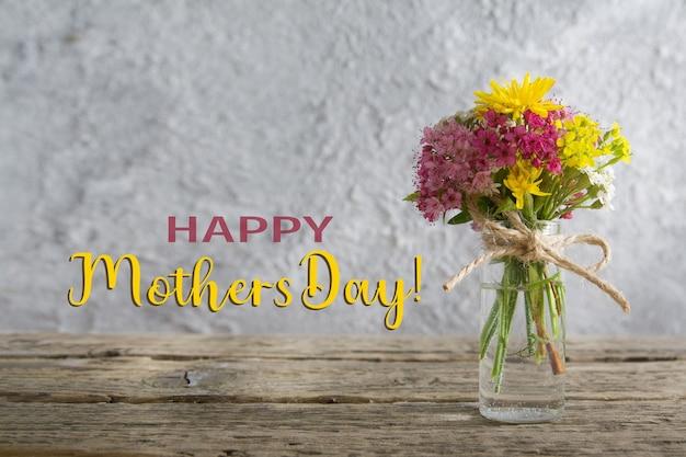 Un bouquet di fiori di campo in una bottiglia di vetro con congratulazioni per la festa della mamma