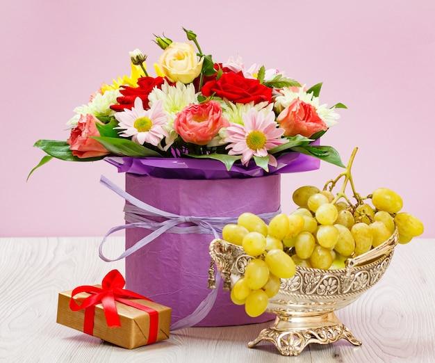Bouquet di fiori di campo, uva e una confezione regalo sulle tavole di legno.