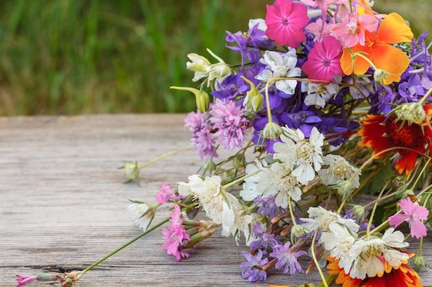 Bouquet di fiori di campo sulla vecchia tavola di legno con uno sfondo naturale.