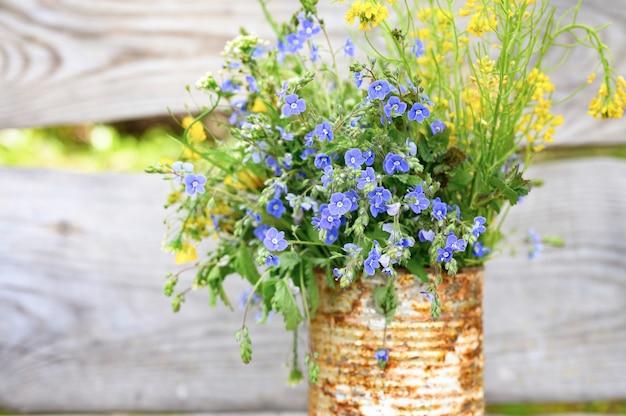 Un bouquet di fiori di campo in un vaso rustico arrugginito contro assi di legno.