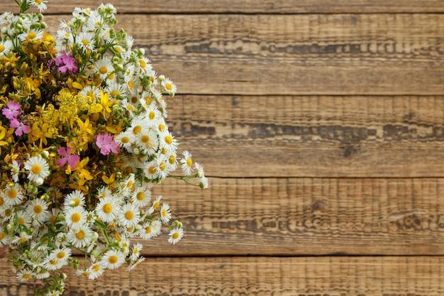Bouquet di fiori di campo con vecchie tavole di legno sullo sfondo.