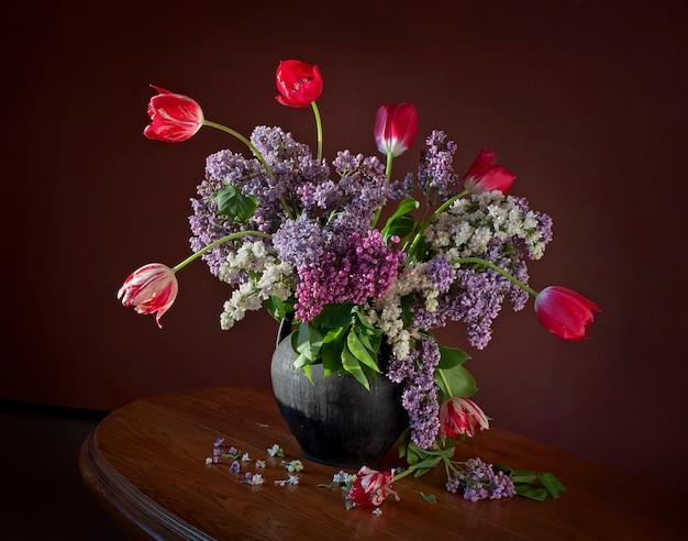 Bouquet con rami fioriti di lillà e tulipani in una brocca di argilla su un tavolo di legno.