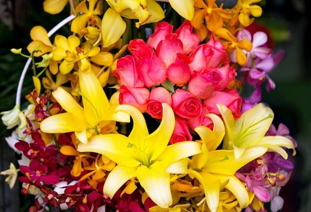 Bouquet con rose rosse, giglio e orchidea