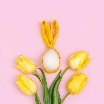 Bouquet di fiori gialli tulipano e uova di pasqua in legno con orecchie in tessuto come coniglietto