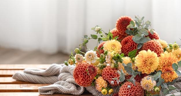 Un bouquet di crisantemi gialli e arancioni su uno sfondo sfocato.