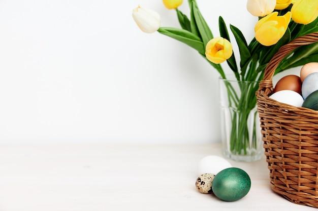 Un mazzo di tulipani gialli e immagini di uova di pasqua su un tavolo luminoso al chiuso