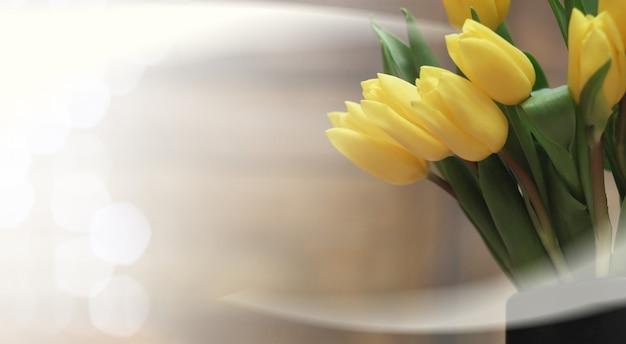 Mazzo di tulipani gialli in un vaso sul pavimento