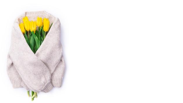 Bouquet di tulipani gialli su sfondo bianco maglione lavorato a maglia con posto per testo, vista dall'alto, bouquet di tulipani gialli per la giornata della donna, concetto di fiori primaverili