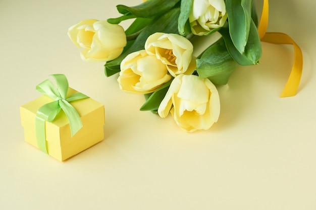 Mazzo dei tulipani gialli con il contenitore di regalo su luce