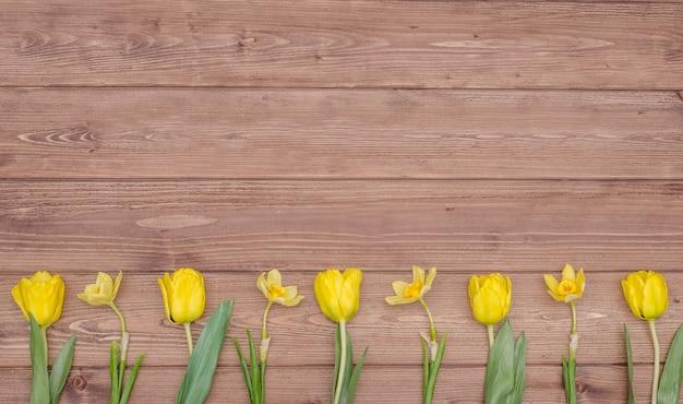 Bouquet di tulipani gialli su sfondo di legno, con spazio di copia