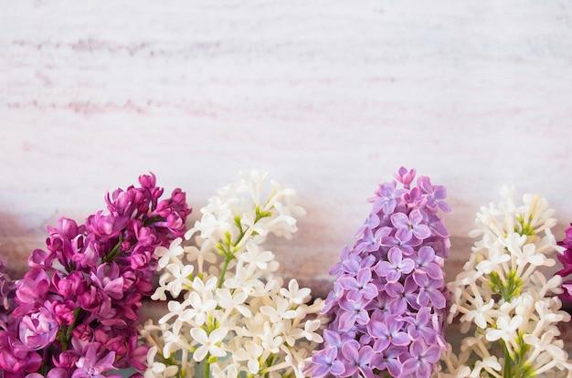 Mazzi di fiori lilla, bianchi e rosa su uno sfondo a trama leggera con spazio per le copie