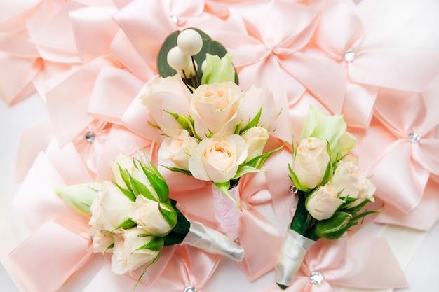 Boutonniere per lo sposo e testimoni dello sposo sullo sfondo di fiocchi rosa di stoffa
