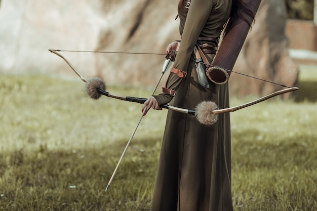 Primo piano di arco e freccia, arciere femminile.