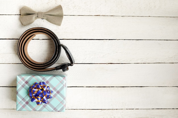 Farfallino, cintura e contenitore di regalo verde sulla tavola di legno bianca con lo spazio della copia