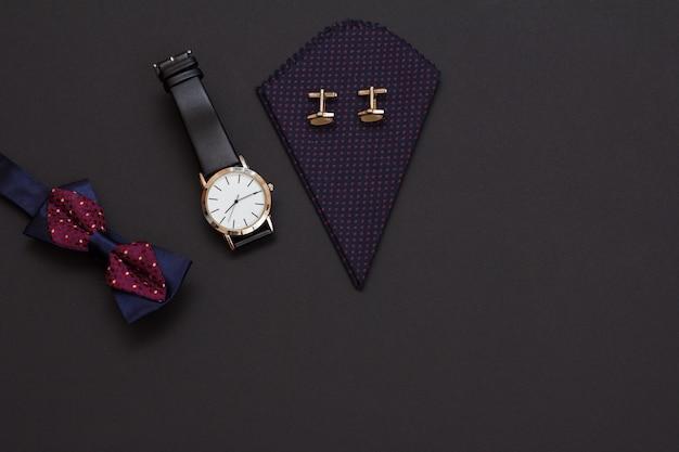 Papillon, orologio con cinturino in pelle nera e fazzoletto con gemelli su sfondo nero. accessori per uomo. vista dall'alto.