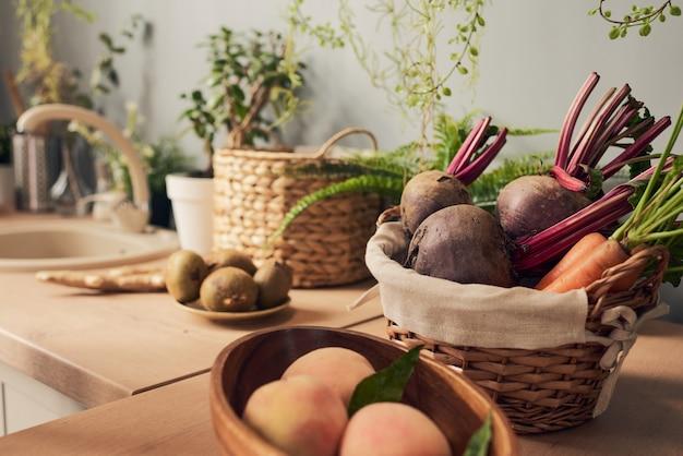 Ciotola e cestino con frutta e verdura fresca sul tavolo