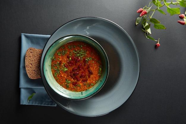 Ciotola di zuppa di fagioli con peperoncino in una ciotola e pane sulla tavola nera