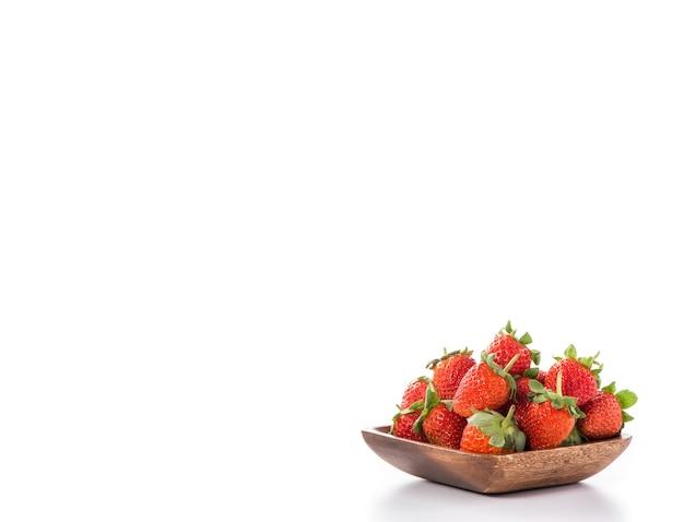 Una ciotola di belle fragole isolate su fondo bianco con il percorso di ritaglio, fine su, macro.