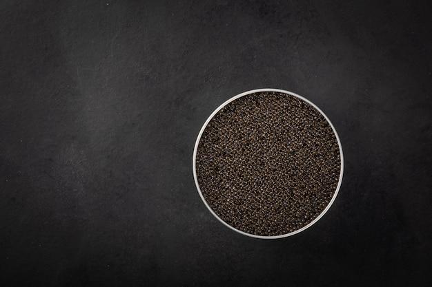 Ciotola di caviale nero di storione su una superficie blu scuro.vista dall'alto