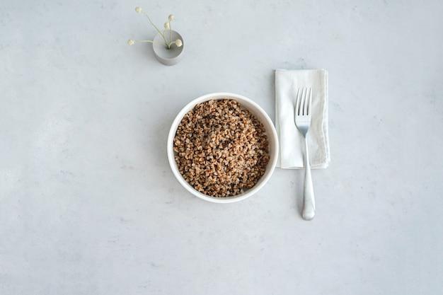 Ciotola di grano saraceno su sfondo di cemento in stile minimalista dieta equilibrata e cibo sano