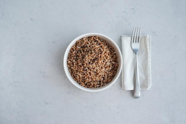 Ciotola di grano saraceno su uno sfondo di cemento in stile minimalista dieta equilibrata cibo vegetariano