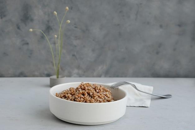 Ciotola di grano saraceno su un cemento in stile minimalista concetto di una dieta equilibrata e cibo sano