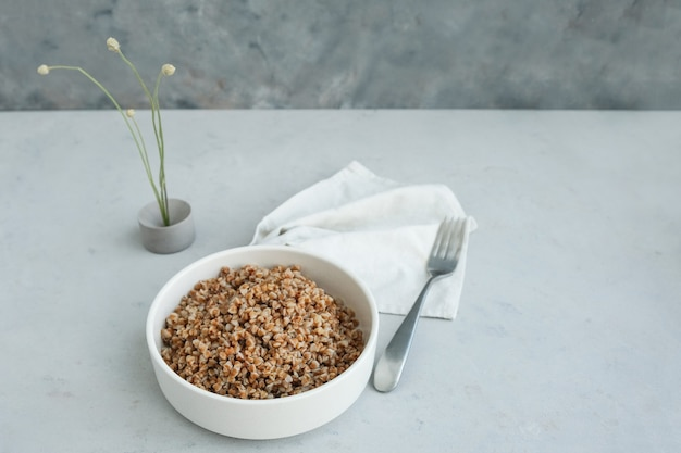 Ciotola di grano saraceno su uno sfondo di cemento grigio in stile minimalista superiore spazio sano copia copy