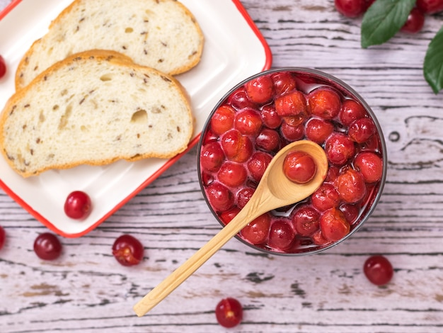 Una ciotola di marmellata di ciliegie e pane di farina grossolana su un tavolo di legno
