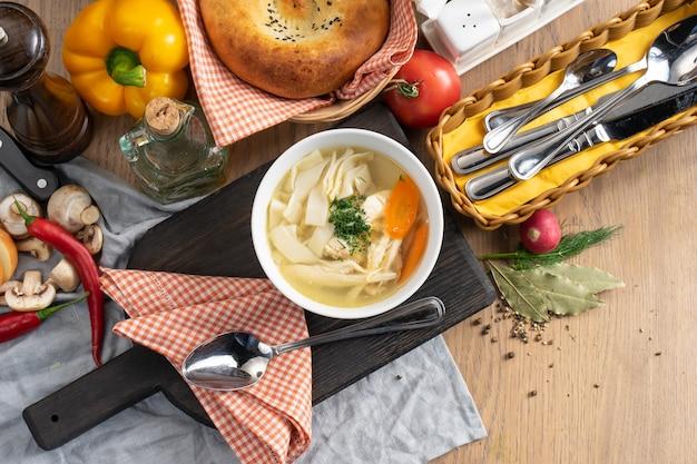 Una ciotola di brodo di pollo con pasta, carote e aneto su un tagliere di legno