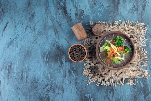 Ciotola di zuppa di pollo su un tovagliolo di tela, sullo sfondo blu.
