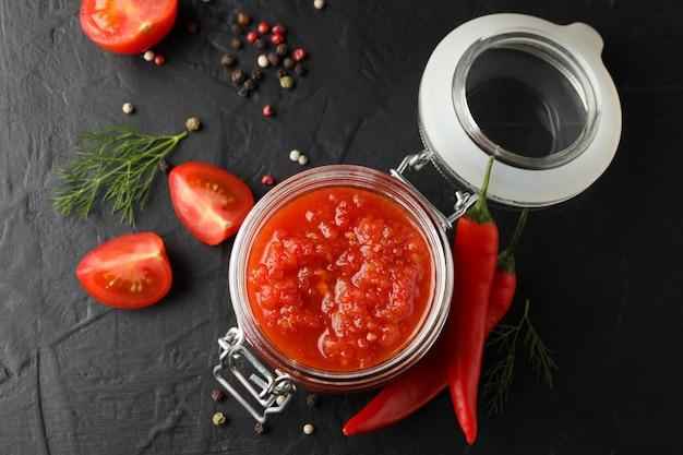Ciotola di salsa di peperoncini rossi, ingredienti su fondo nero, fine su. vista dall'alto