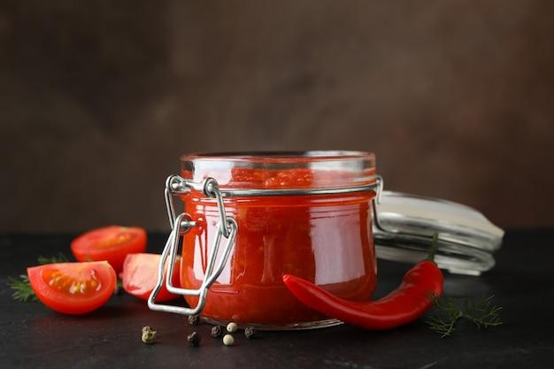 Ciotola di salsa di peperoncino, ingredienti su sfondo nero, spazio per il testo