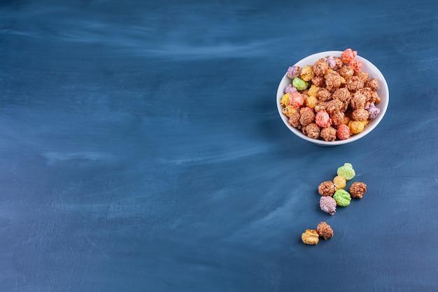 Ciotola di palline di cereali colorate poste su uno sfondo blu.