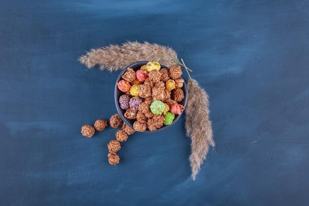 Ciotola di palline di cereali colorate disposte su un blu.