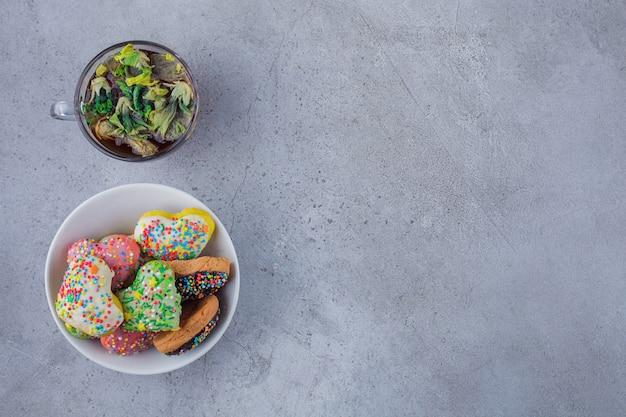 Ciotola di deliziosi biscotti con spruzza e tazza di tè su sfondo di pietra.