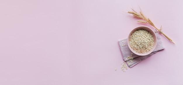 Ciotola di fiocchi d'avena secchi con spighe di grano su sfondo chiaro. cucinare il concetto di porridge di avena. vista dall'alto