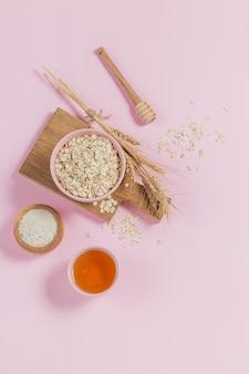 Ciotola di fiocchi d'avena secchi con miele, farina d'avena e spighe di grano su sfondo chiaro. pelle sana, cura del viso e del corpo. spa e concetto di sauna. lay piatto