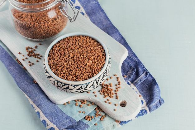 Ciotola di semole di grano saraceno crudo secco e vaso di vetro su uno sfondo azzurro. cucinare il concetto di porridge di grano saraceno.